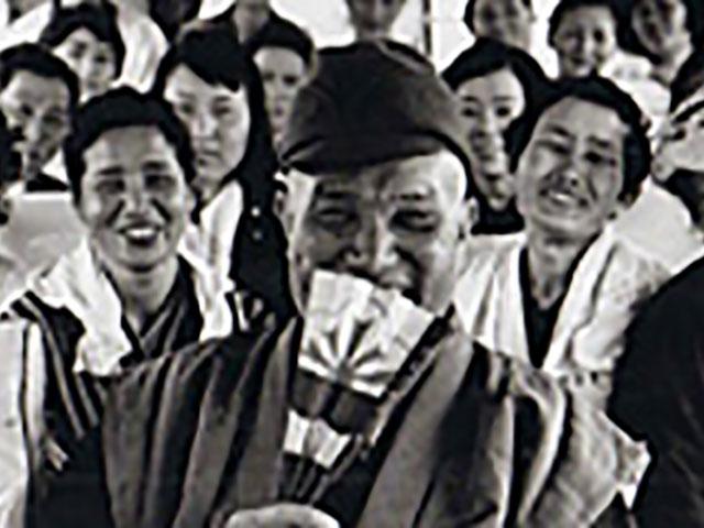 昭和33年、バスの中で信徒に囲まれ、笑顔の親先生