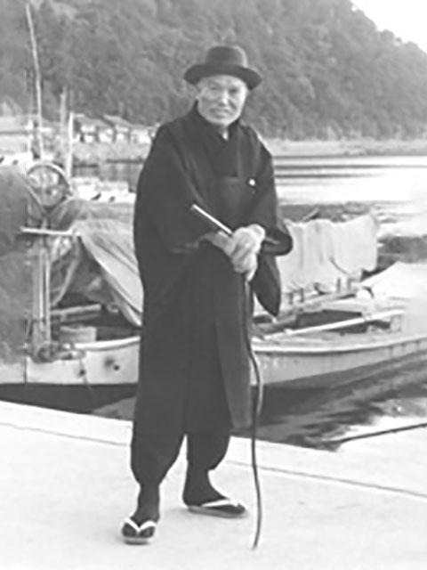 昭和35年12月、引本念法教会前の港に立つ親先生(当時親先生75歳)